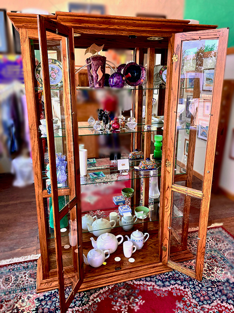 Large glass curio cabinet with various colorful glass items.